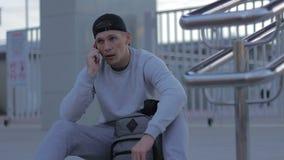 El hombre joven de la aptitud habla en el teléfono en la cámara lenta de la ciudad almacen de video