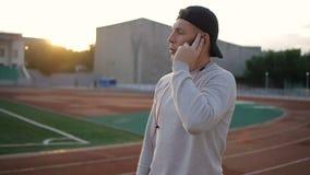 El hombre joven de la aptitud habla en el teléfono en pista del estadio en la cámara lenta almacen de video
