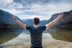 El hombre joven de la libertad da para arriba en un lago de la montaña Foto de archivo