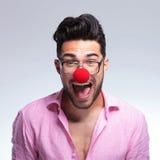 El hombre joven de la moda grita con una nariz roja Fotografía de archivo libre de regalías
