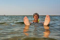 El hombre joven flota en agua con los pies para arriba Foto de archivo