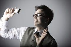 El hombre joven de risa hace un selfie con una cámara compacta Foto de archivo