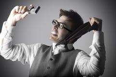 El hombre joven de risa hace un selfie con una cámara compacta Imagen de archivo libre de regalías