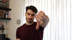 El hombre joven decepcionado o descontentado que hace el pulgar abajo firma metrajes