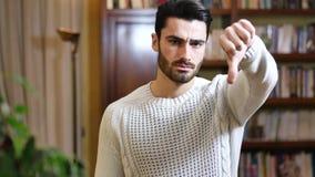 El hombre joven decepcionado o descontentado que hace el pulgar abajo firma almacen de metraje de vídeo