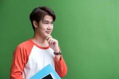 El hombre joven del adolescente que sostiene la tableta y el cuaderno y enrarecen Foto de archivo libre de regalías