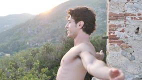 El hombre joven del ajuste atlético, hermoso al aire libre en el país que hace estirar ejercita almacen de metraje de vídeo