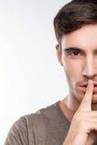 El hombre joven del ajuste atractivo tiene un secreto grande Imagen de archivo libre de regalías