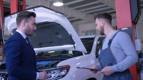 El hombre joven del cliente entrega llaves autos al técnico para la reparación profesional y sacude las manos cerca del automóvil almacen de video