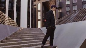 El hombre joven del inconformista con la cara tatúa caminar en las escaleras en el distrito financiero metrajes