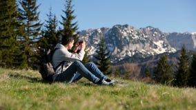 El hombre joven del inconformista con la mochila se coloca encima de la montaña, disfrutando de la visión asombrosa El turista ma almacen de video