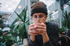 El hombre joven del inconformista con los vidrios calentó la bebida caliente mientras que la llevaba a cabo en sus manos Fotografía de archivo libre de regalías