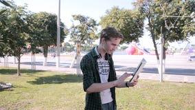 El hombre joven del inconformista que usa la tableta en el parque de la ciudad que juega el pokemon va metrajes