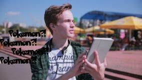 El hombre joven del inconformista que usa la tableta en la ciudad que juega el pokemon va almacen de video