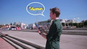 El hombre joven del inconformista que usa la tableta en la ciudad que juega el pokemon va metrajes