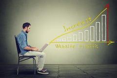 El hombre joven del individuo de las TIC que trabaja en el cuaderno tiene un plan para aumentar tráfico del sitio web Imagen de archivo libre de regalías