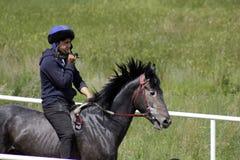 El hombre joven del Kazakh está montando un caballo breeded puro del Kazakh Fotos de archivo