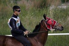 El hombre joven del Kazakh está montando un caballo marrón breeded y se está preparando para competir con Imágenes de archivo libres de regalías