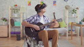 El hombre joven del retrato inhabilitó en una silla de ruedas en vidrios de la realidad virtual que el músico toca la guitarra el almacen de video