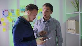 El hombre joven dice a empleados que está escrito en la tableta metrajes