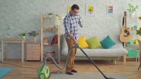 El hombre joven discapacitado sin una mano está limpiando la casa con un aspirador metrajes