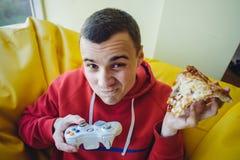 El hombre joven divertido que juega al videojuego en la palanca de mando y come la pizza deliciosa Fotografía de archivo