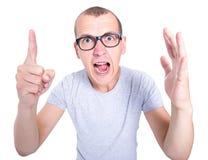 El hombre joven divertido y enojado en vidrios con los apoyos en los dientes grita Fotografía de archivo libre de regalías