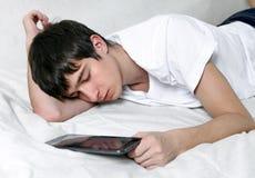 El hombre joven duerme con la tableta Foto de archivo