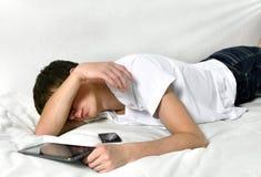 El hombre joven duerme con la tableta Imágenes de archivo libres de regalías
