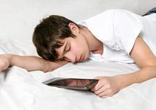 El hombre joven duerme con la tableta Fotos de archivo