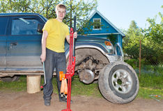 El hombre joven, el adolescente substituye una rueda en un coche campo a través Imagen de archivo