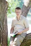 El hombre joven (el alumno, el estudiante) lee el libro en la orilla del río Foto de archivo