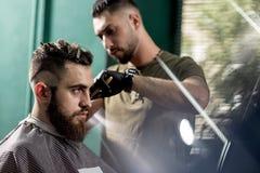 El hombre joven elegante con la barba se sienta en una peluquería de caballeros El peluquero en guantes negros afeita los pelos e imagenes de archivo