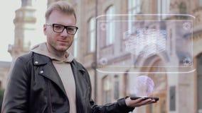 El hombre joven elegante con los vidrios muestra que un holograma conceptual apila del dinero almacen de metraje de vídeo