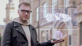 El hombre joven elegante con los vidrios muestra un chasis conceptual del holograma almacen de metraje de vídeo