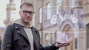 El hombre joven elegante con los vidrios muestra un chasis conceptual del holograma 3D metrajes