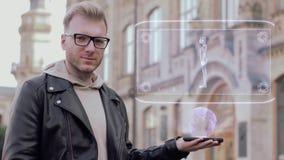 El hombre joven elegante con los vidrios muestra a un cuerpo conceptual de la mujer del holograma