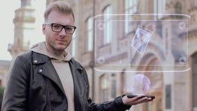 El hombre joven elegante con los vidrios muestra un procesador conceptual del ordenador del holograma almacen de metraje de vídeo
