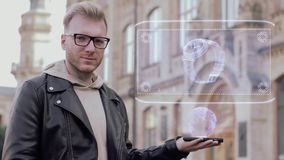 El hombre joven elegante con los vidrios muestra un reloj conceptual del holograma