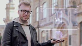 El hombre joven elegante con los vidrios muestra una caja fuerte conceptual del holograma con el dinero almacen de video