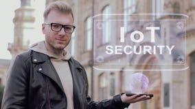 El hombre joven elegante con los vidrios muestra una SEGURIDAD conceptual de IoT del holograma almacen de video