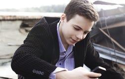 El hombre joven elegante con el teléfono lee el mensaje Fotografía de archivo