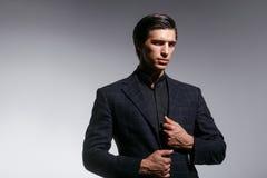 El hombre joven elegante en traje, arregla su traje, concepto de la alta moda, en un fondo blanco Visi?n horizontal foto de archivo libre de regalías