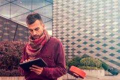 El hombre joven elegante trabaja en la tableta al aire libre en espacio público urbano foto de archivo libre de regalías