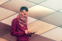 El hombre joven elegante trabaja en la tableta al aire libre en espacio público urbano fotos de archivo libres de regalías