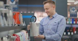 El hombre joven elige la caldera eléctrica para su nuevo hogar en tienda de dispositivos metrajes