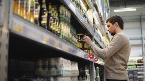 El hombre joven elige una cerveza para el partido con los amigos en el supermercado almacen de metraje de vídeo