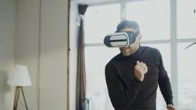 El hombre joven emocionado con el baile de las auriculares de la realidad virtual y juega al videojuego 360 en casa foto de archivo