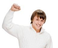 El hombre joven emocionado golpea el brazo apretado aire de los puños con el pie Foto de archivo