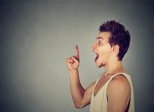 El hombre joven emocionado tiene una nueva idea que destaca el finger Foto de archivo